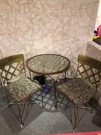 Iron circle table with glass top and 2 chairs.
