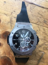 Round black chronograph watch with black rubber strap