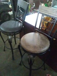 Two brown leather and black leather bar stools with steel frame