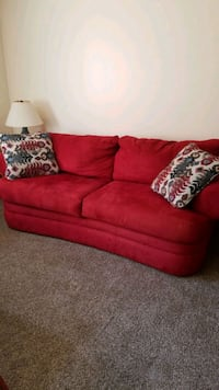 Nice red couch with two pillows
