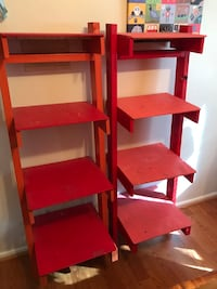 Two red wooden 3-layered shelves
