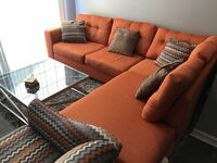 Orange fabric sectional with throw pillows, matching chair, and table Cincinnati, 45248