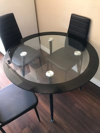 Round glass dining table with 4 black leather chairs La Habra, 90631