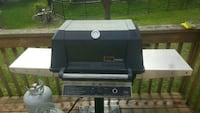 black and grey gas grill and two grey propane tank