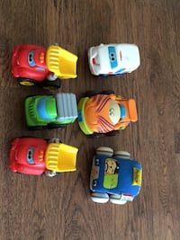 four assorted plastic toy cars