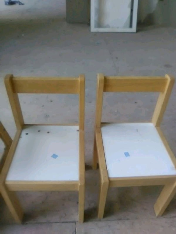 two brown wooden framed white padded chairs a5fdcd82-2155-43fe-91bc-f52e173f288d