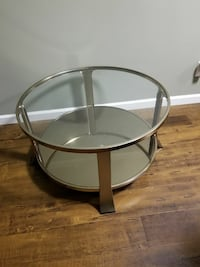 round clear glass top table with brown wooden base