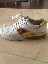 unpaired white and brown Michael Kors sneaker
