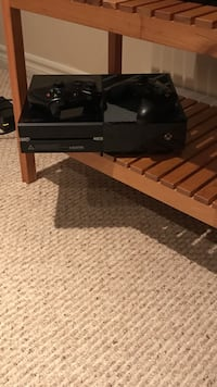 Black Xbox One console with two controllers