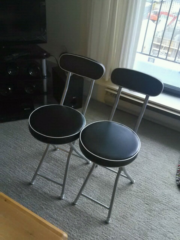 two black leather padded bar stools