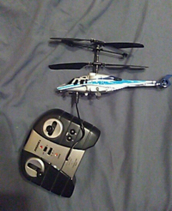 white, blue, and grey helicopter toy with black and grey radio controller