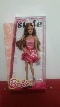 Barbie doll in pink dress in box.