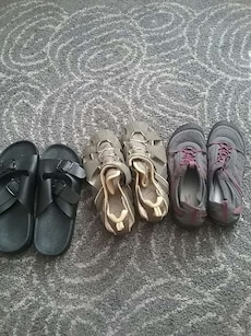 pair of black leather slide sandals; two pairs of brown and gray water sandals