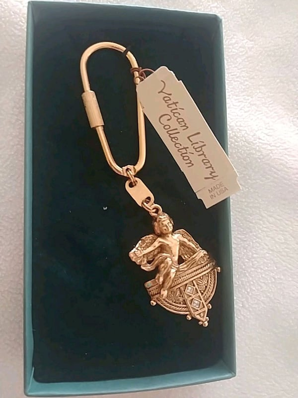 A keychain with a angel and gold color  5f7e271e-0e51-45e0-9224-c68a1c4f2907