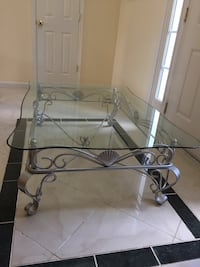 Serpentine Style Glass Top Coffee Table w/ Silver Iron Scroll Base that features Shell Motif