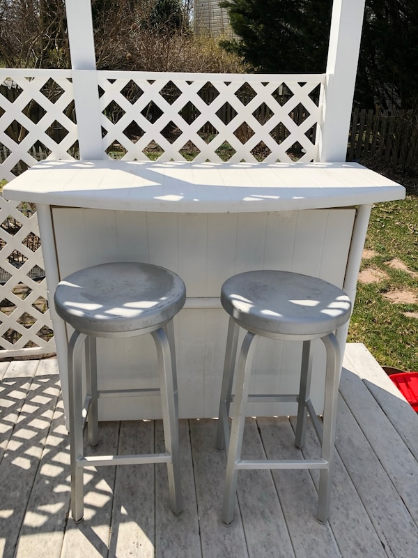 Outdoor Bar and 2 Swivel Stools. Bar has shelf on the inside for glasses, bottles, etc.  There is a small crack near the bottom but it has been there for 4 years and is not a problem. Bar is very study and weatherproof. Perfect for entertaining