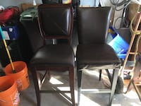 Two brown leather bar stools
