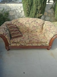 brown, pink, and green wooden padded floral loveseat