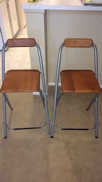 two black metal framed brown wooden folding chairs