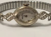 Lucien Piccard  Oval Shape Ladies Watch  12 Diamonds  14K White Gold  23.79 grams  Serial number: 22418  Hand-Winding  Stainless Steel Speidel Band  CIRCA 1950's  Runs and keeps accurate time  Was just serviced less than a year ago
