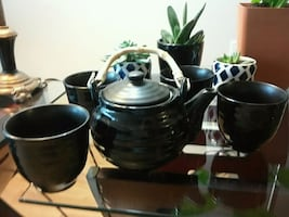 black and gray ceramic tea set with four cups