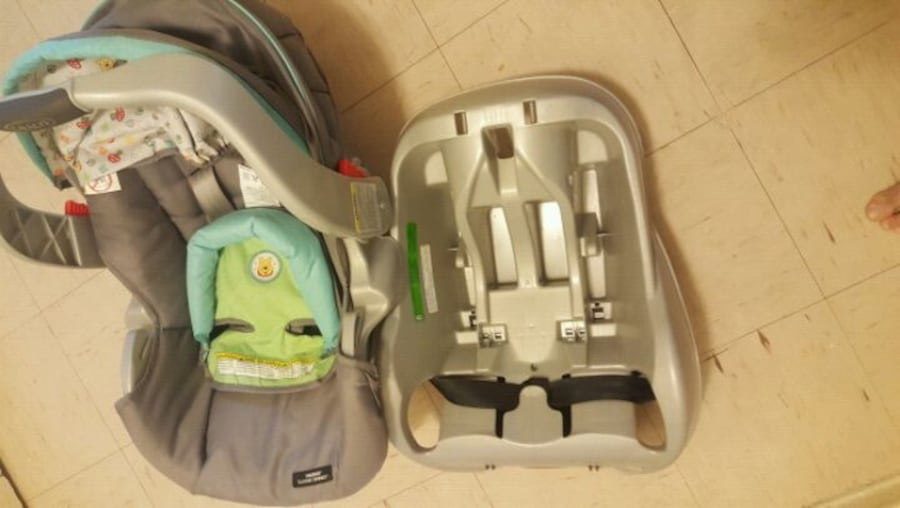 baby's gray and green car seat carrier. 23d2b1c5-7cad-4d70-937b-3b0056c511b0