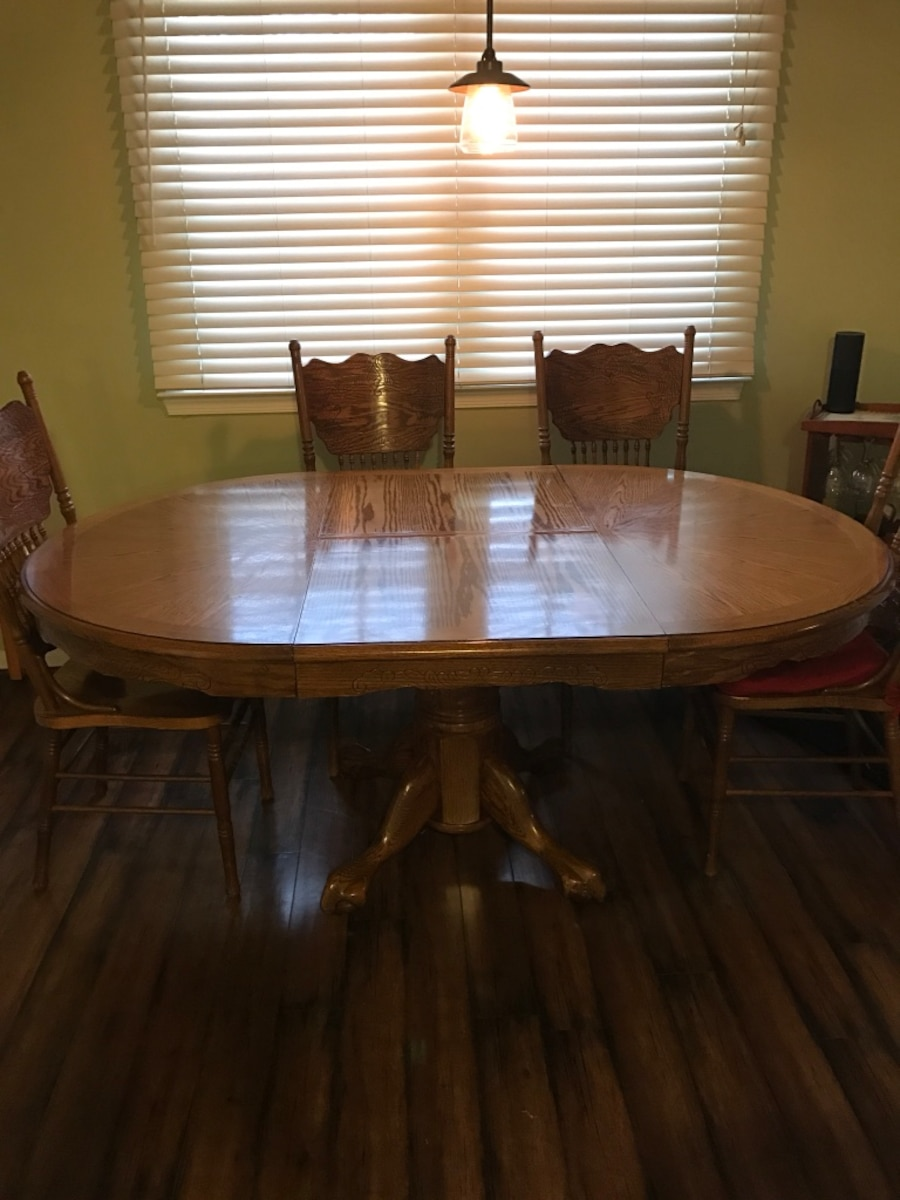 Used brown wooden round table with four dining chairs in