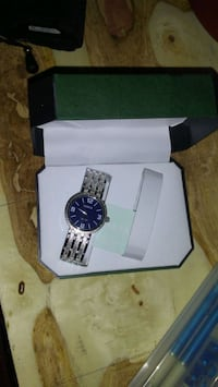 round silver chronograph watch with link bracelet in box