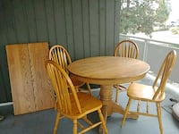 round brown wooden pedestal table with four chairs Kelowna, V1X 3E7