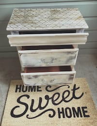 gray wooden 3-drawer chest and brown with Home sweet Home printed area mat