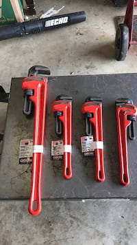 Four red and black pipe wrenches