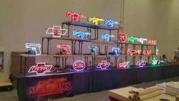 neon signs in the shape of guns ar15, 1911s, glocks, guns and cars
