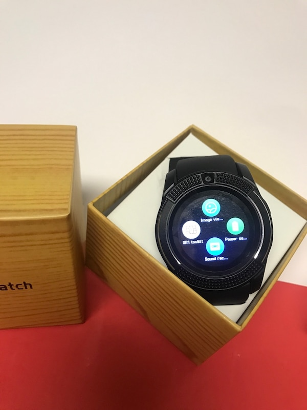 round black smartwatch with black rubber strap in box