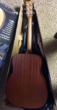 Brown acoustic guitar with black case
