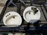 two white ceramic sinks with faucet