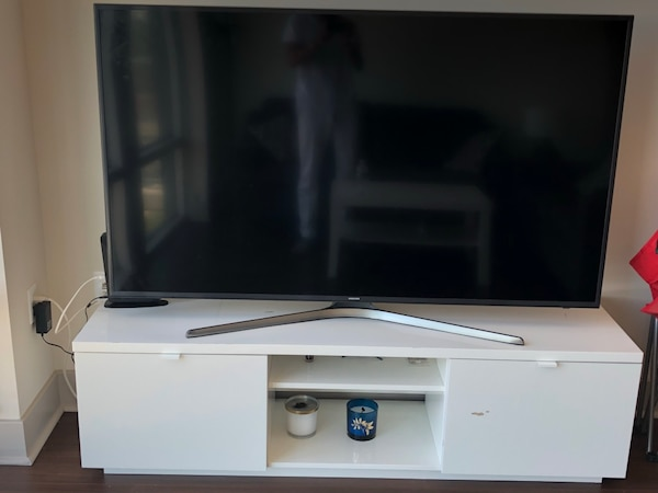 black flat screen TV; white wooden TV stand