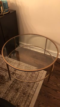 round clear glass-top table with brown steel base 46 km