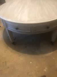 Shabby, lightly distressed coffee table. 40 inches round. Has gray undertones - reclaimed wood look. On wheels and has 4 roomy drawers