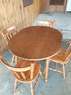 four brown wooden chairs and oval brown wooden dining table