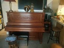 brown upright piano with chair