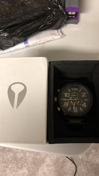 Round black chronograph watch with black strap in box
