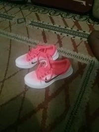 pair of pink-and-white Nike sneakers Kingston