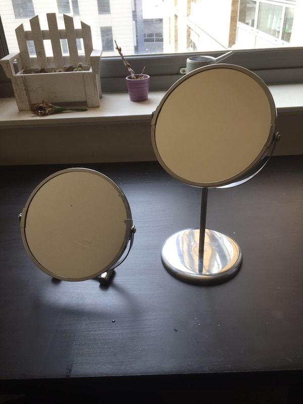 two round brown wooden framed mirrors