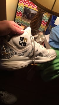 unpaired white and black Adidas basketball shoe