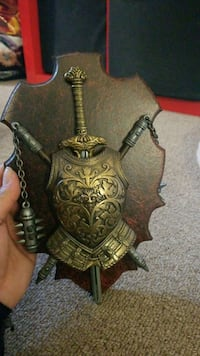 brass-colored flail, sword and armor wall decor