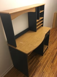 brown and black wooden single pedestal computer desk with hutch