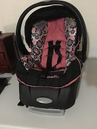 baby's black and pink Evenflo car seat carrier