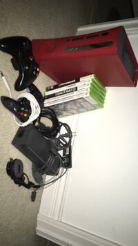 Red xbox 360 console with controller and games.