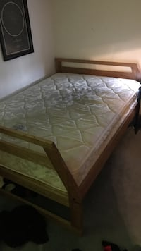 Brown wooden bed frame with bed mattress