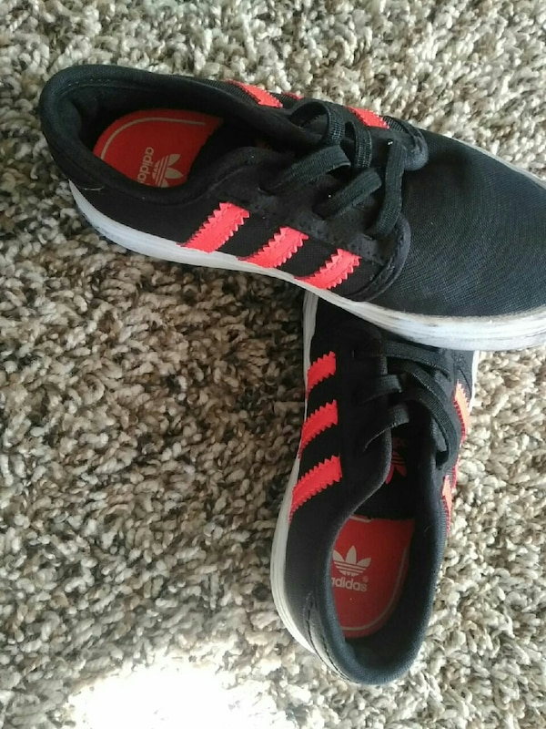 black-and-red Adidas low-top sneakers